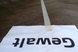 """Papier mit Aufschrift """"Gewalt"""" auf dem Boden"""